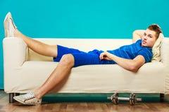 Corps convenable de jeune homme détendant sur le divan après la formation photos libres de droits
