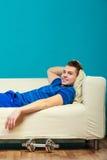 Corps convenable de jeune homme détendant sur le divan après la formation photo libre de droits