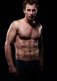Corps d'un jeune homme musculaire, fond d'obscurité de studio Image libre de droits