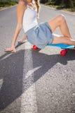 Corps de jeune femme s'asseyant sur sa planche à roulettes Photographie stock libre de droits