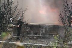 Corps de sapeurs-pompiers dans l'action pendant les entrepôts brûlants avec les produits en plastique Images stock