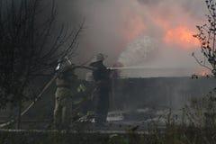 Corps de sapeurs-pompiers dans l'action pendant les entrepôts brûlants avec les produits en plastique Image libre de droits