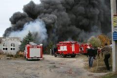 Corps de sapeurs-pompiers dans l'action pendant les entrepôts brûlants avec les produits en plastique Photographie stock