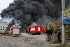 Corps de sapeurs-pompiers dans l'action pendant les entrepôts brûlants avec les produits en plastique Photo stock
