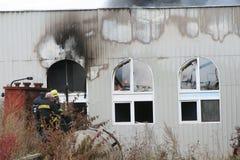 Corps de sapeurs-pompiers dans l'action pendant les entrepôts brûlants avec les produits en plastique Photographie stock libre de droits
