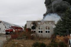 Corps de sapeurs-pompiers dans l'action pendant les entrepôts brûlants avec les produits en plastique Photos stock