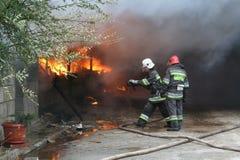 Corps de sapeurs-pompiers dans l'action pendant les entrepôts brûlants avec les produits en plastique Image stock