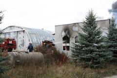 Corps de sapeurs-pompiers dans l'action pendant les entrepôts brûlants avec les produits en plastique Photo libre de droits