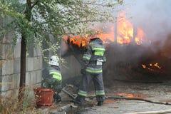 Corps de sapeurs-pompiers dans l'action pendant les entrepôts brûlants avec les produits en plastique Images libres de droits
