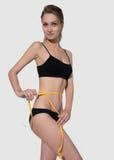 Corps mince de femme dans la mesure noire de sous-vêtements d'isolement sur le blanc image stock