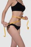 Corps mince de femme dans la mesure noire de sous-vêtements sur le backgroud blanc Image libre de droits