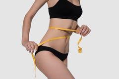 Corps mince de femme dans la mesure noire de sous-vêtements sur le blanc Photo stock