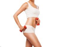Corps sexy de femme de forme physique faisant des exercices avec le rouge Image libre de droits