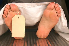 Corpse. Caucasian feet with a toe tag in a morgue royalty free stock photography