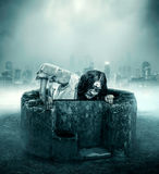 The corpse gets out of a well. The corpse woman gets out of a well against the city background Stock Image