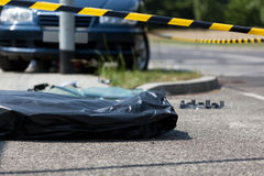 Corpse in plastic bag after car accident. Horizontal stock photos
