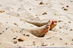 Corpse in the sand. The feet of a corpse that protrude from the sand Stock Image