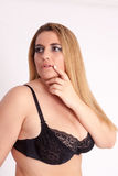 Corpulent, busty woman with long blonde hair and black bra Stock Photo