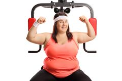 Corpulent woman showing muscles with an exercising machine stock photos