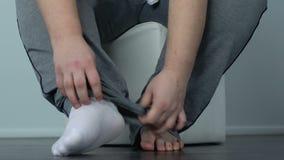 Corpulente hulking mannelijke het zetten sokken die op stoel, bovenmatig gewichtsprobleem zitten stock footage