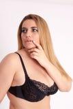Corpulente, rondborstige vrouw met lang blondehaar en zwarte bustehouder Stock Foto
