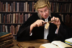 Corpus delictum. Mature judge holding evidence of a crime in court royalty free stock photography