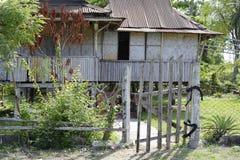 Corra abajo de la cerca de madera blanqueada casa abandonada de la descomposición de la granja en la playa Foto de archivo