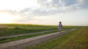 Corra feliz, el niño femenino sonriente, funcionamientos de la niña a lo largo del camino del campo, niño corriente, niño feliz q almacen de metraje de vídeo
