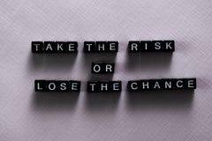 Corra il rischio o perda la probabilità sui blocchi di legno Concetto di ispirazione e di motivazione immagini stock