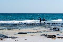 Surfers in the beach of Corralejo Bay. Corralejo, Fuerteventura, Canary Islands, Spain - February 17, 2018: Surfers in the beach of Corralejo Bay at morning Stock Images
