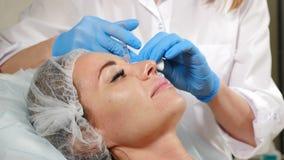 correção Não-cirúrgica da forma do nariz Uma moça durante o procedimento da beleza Feche acima das mãos do esteticista no azul video estoque