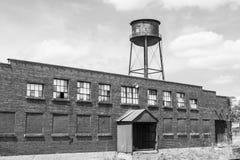 Correa abandonada Warehouse auto del moho y fábrica con I llevado, roto y olvidado de la torre de agua - Imagenes de archivo