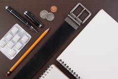 Correa accesoria con la pluma, el cuaderno y el chicle en la tabla de madera Fotografía de archivo libre de regalías