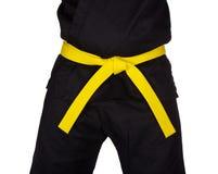 Correa amarilla del karate atada alrededor del uniforme del negro del torso Imagenes de archivo