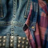 correa de cuero en un par descolorado de tejanos y de detalles de la camisa a cuadros roja y azul fotos de archivo
