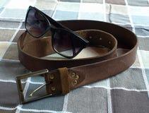 Correa de cuero, gafas de sol, fondo a cuadros Foto de archivo