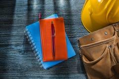 Correa de cuero de la herramienta del casquillo de seguridad de la pluma de los cuadernos en el tablero de madera fotos de archivo libres de regalías