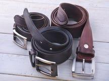 Correa de cuero de moda del ` s de los hombres Artilugios y accesorios para los hombres en fondo de madera ligero Fotos de archivo libres de regalías