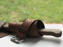 Correa de cuero vieja una serpentina en el hacha Hacha y correa - después del trabajo Imagen de archivo libre de regalías