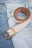 Correa de cuero y mezclilla azul del dril de algodón fotografía de archivo libre de regalías