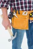 Correa de la herramienta del reparador que lleva mientras que sostiene el martillo Foto de archivo