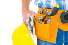 Correa de la herramienta del trabajador que lleva manual mientras que sostiene guantes y el casco Fotos de archivo libres de regalías