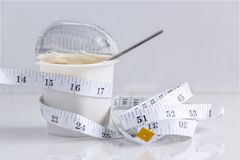Correa de Measuring Tape del sastre en una taza de yogur El concepto de yogur como la comida, la atención sanitaria y formas fotografía de archivo