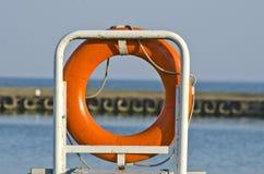 Correa de vida anaranjada del anillo de la boya de vida en puerto Imágenes de archivo libres de regalías