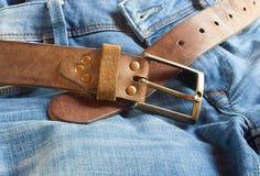 Correa marrón de cuero con vaqueros Imagen de archivo libre de regalías