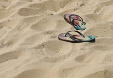 Correas coloridas de la chancleta en una playa arenosa Fotografía de archivo