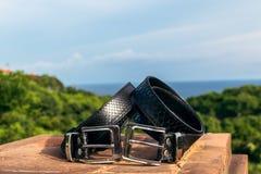 Correas de cuero del snakeskin de lujo de la moda al aire libre Correas de Python en un fondo tropical foto de archivo