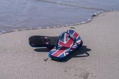 Correas de la chancleta de la bandera en una playa Foto de archivo libre de regalías