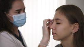 Correcci?n de la ceja El cosmetólogo frota las cejas con un cojín de algodón, desinfección del cliente Vista lateral almacen de video