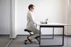 Correct sitting position on kneeling chair Royalty Free Stock Image